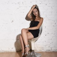 Italian model showing her long legs wearing a tight black dress and shiny silver high heels