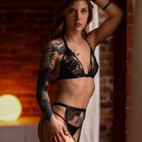 Lovely blue eyed brunette Canadian inked model Carolanne Bergeron wearing see through black lace lingerie on a sensual photoshoot