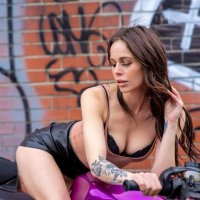 Canadian model Melissa Kara showing sexy cleavage sitting on a bike wearing a short black leather skirt