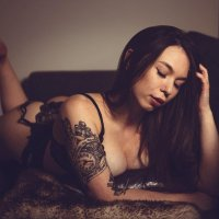 Stunning Finnish inked model Katlin Angela lying on her bed wearing black lace lingerie bare feet showing cleavage for a boudoir photo shoot