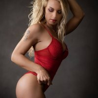 Stunning and hot blonde Dutch inked model Willeke Bartels wearing red lingerie on a sensual boudoir photo session