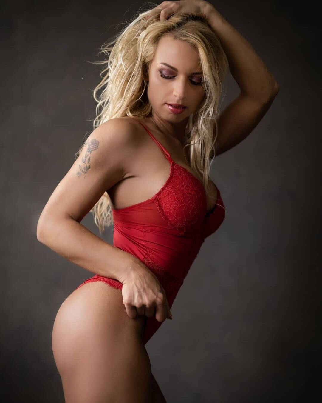 Sexy blonde Dutch tattooed fitness model and mom Willeke Bartels wearing red lingerie holding one arm up on a sensual boudoir photo session