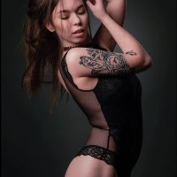 Sexy inked model wearing a black lace nylon body suit posing for a boudoir photo session