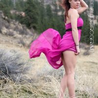 Sexy model BC Mama wearing a short pink dress and black heels in the country showing her hot legs
