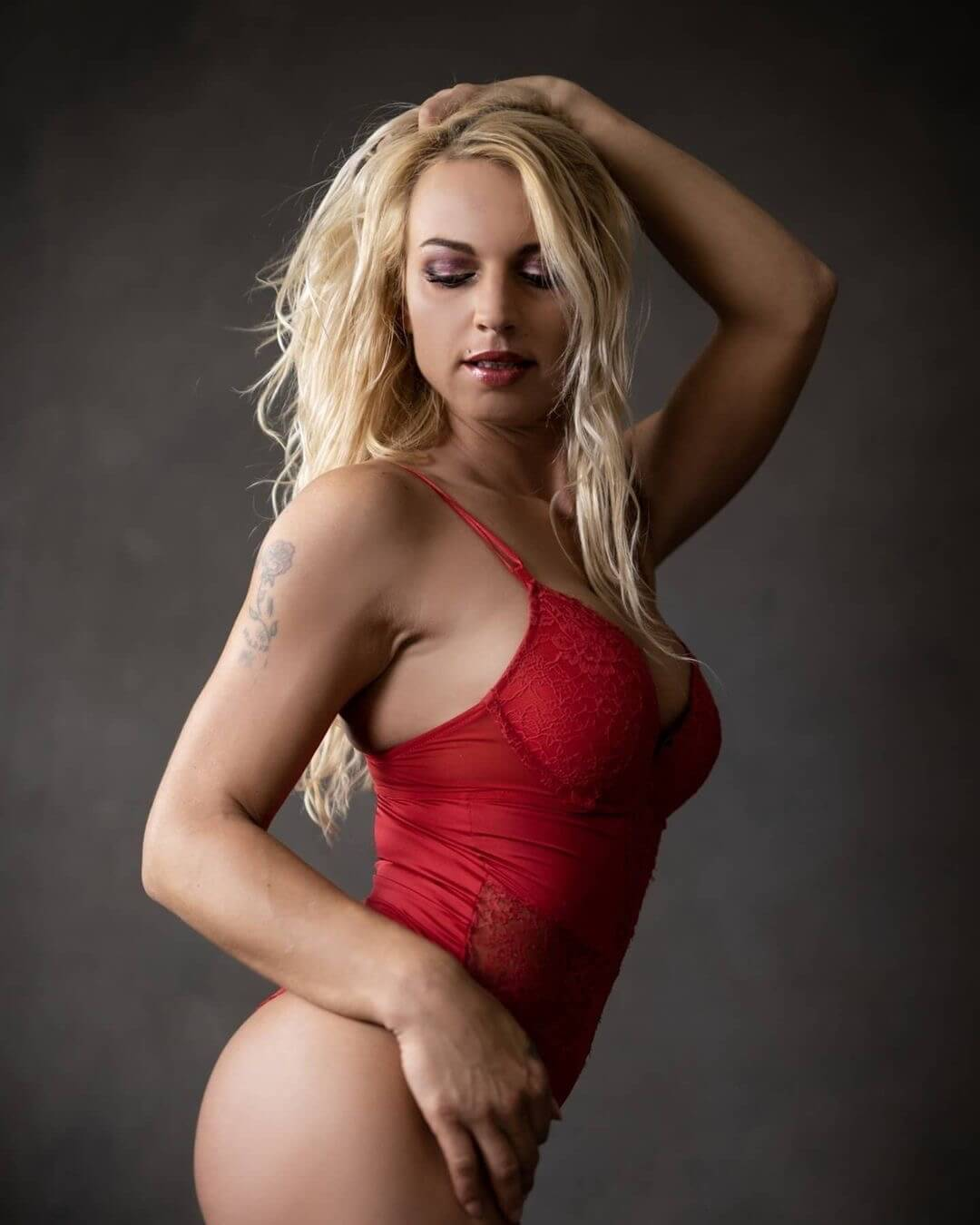 Sexy blonde Dutch inked model Willeke Bartels showing her hot fit mom body wearing red lingerie on a sexy boudoir photo session