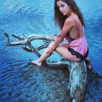 Sexy Canadian model sitting on a log wearing pink satin lingerie showing her hot legs dipping her bare feet in a river