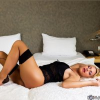 Sexy blonde Dutch model in her bed wearing black lingerie for a sensual boudoir photo session
