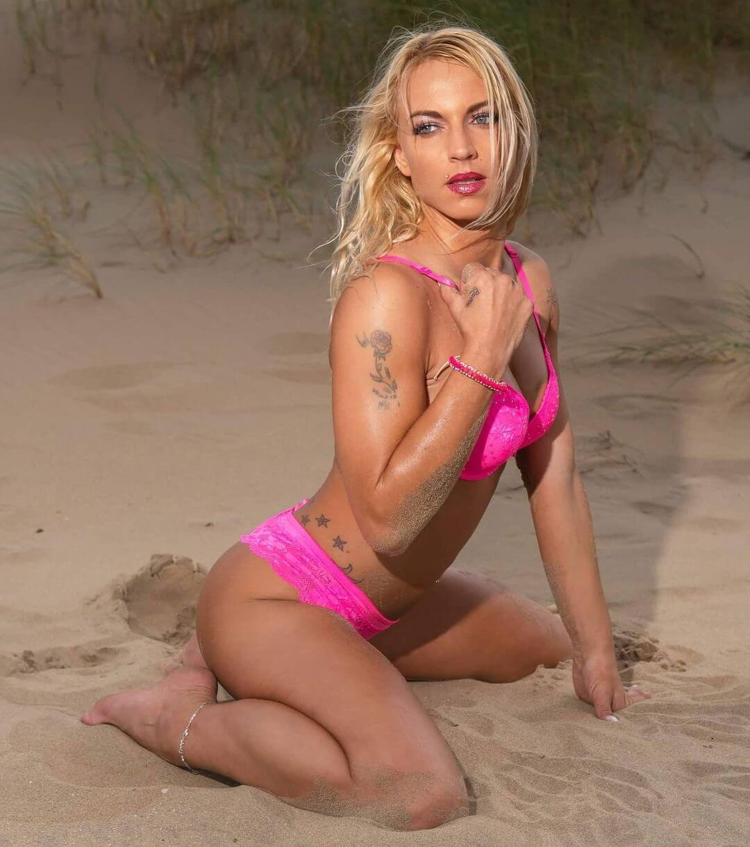Sexy blonde inked model wearing pink kneeling in the sand for a hot beach photo session