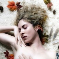 Beautiful blonde model resting in the nude with one arm up showing her shaved armpit surrounded by fall leaves and feathers