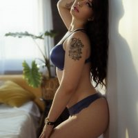 Hot sensual inked model posing in a boudoir session wearing blue lingerie