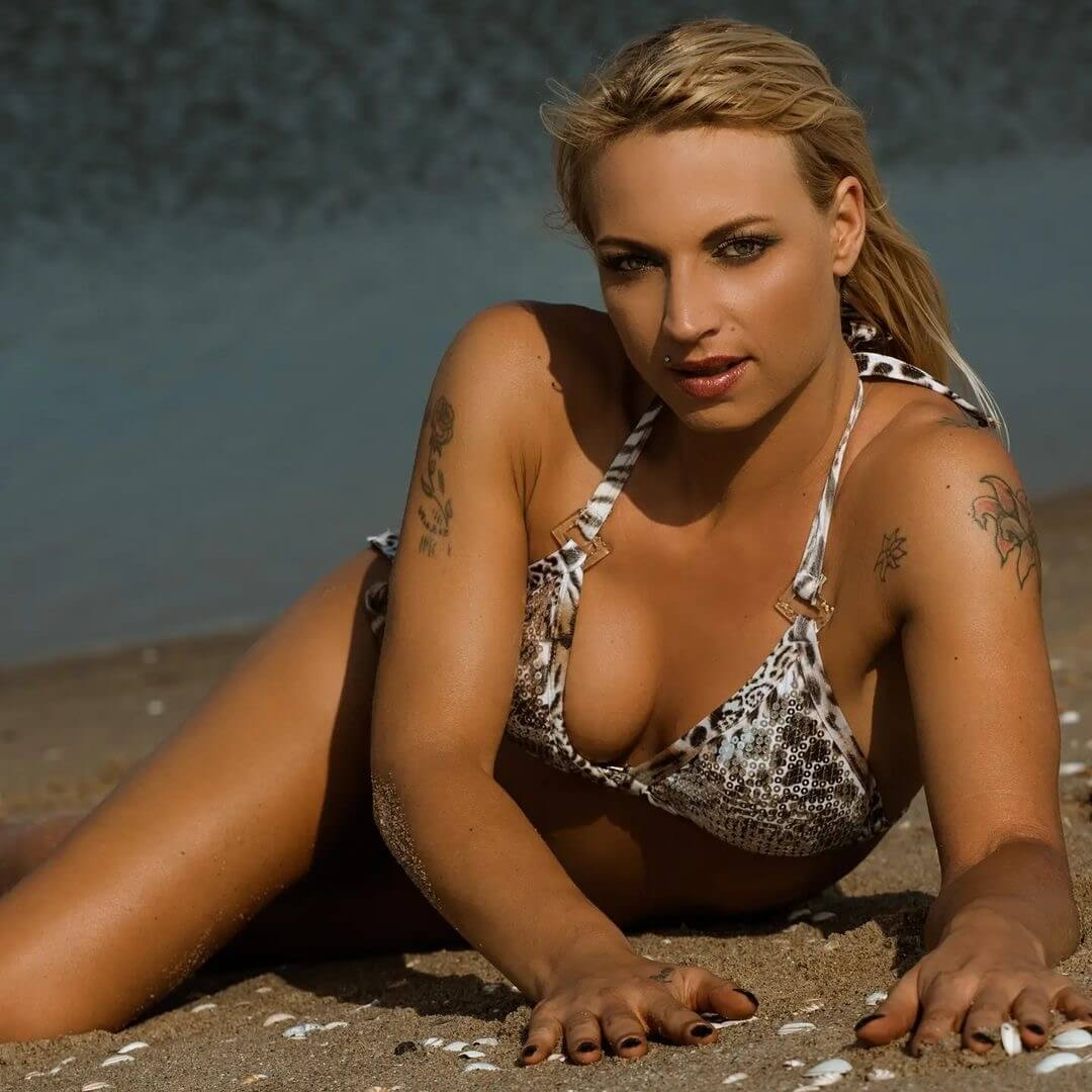 Hot blonde model wearing a leopard printed bikini at the beach lying in the sand showing some sexy cleavage