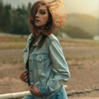 Beautiful young actress and model wearing a denim jacket at the beach