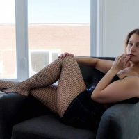 Beautiful young model lounging on a chair wearing a short tight black dress and black fishnets nylons