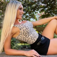 Smiling blonde model wearing a leopard printed top with dark shorts outside on a summer day
