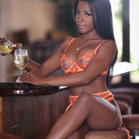 Sexy black model sitting at a bar with her long legs crossed wearing see through peach lingerie pouring herself a glass of wine