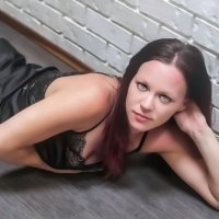 Sensual and sexy blue eyed Canadian model wearing black lingerie lying on the floor showing her hot cleavage