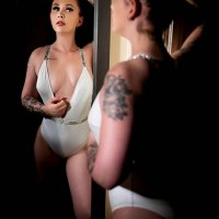Sexy inked model wearing a luxury one piece showing her hot body and cleavage looking at her reflection in a mirror