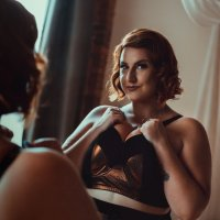 Hot curvy redhead model wearing black luxury lingerie putting her massive cleavage on display in a mirror reflection boudoir photo session