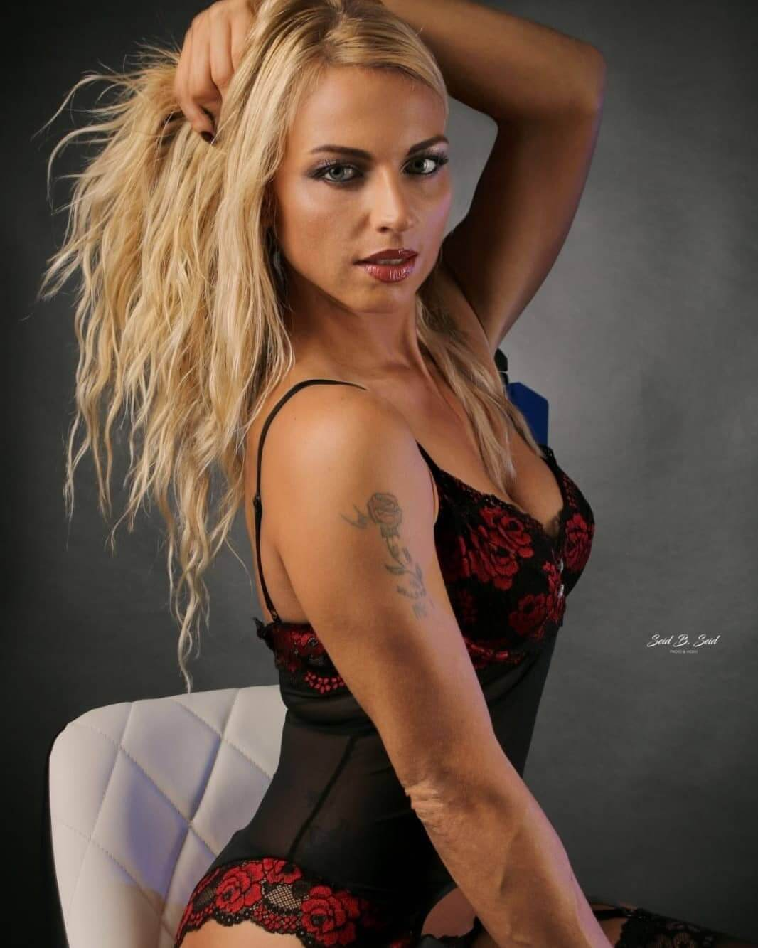 Hot inked blonde Dutch model wearing black and red lingerie in sexy poses for a boudoir photo shoot