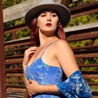 Beautiful red head country girl wearing a blue dress and cowboy boots under the hot sun