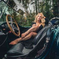 Hot classy blonde sitting bare feet in a classic green Cobra Shelby 67 wearing a tight short black dress showing her long legs