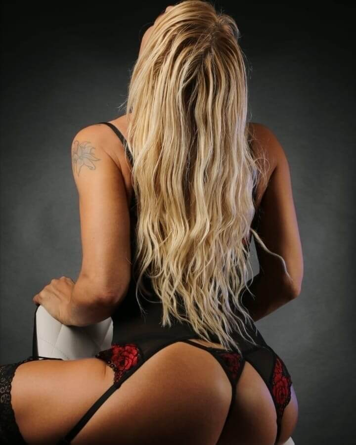 Hot inked blonde Dutch model showing her mom booty wearing black and red lingerie in sexy poses for a boudoir photo shoot