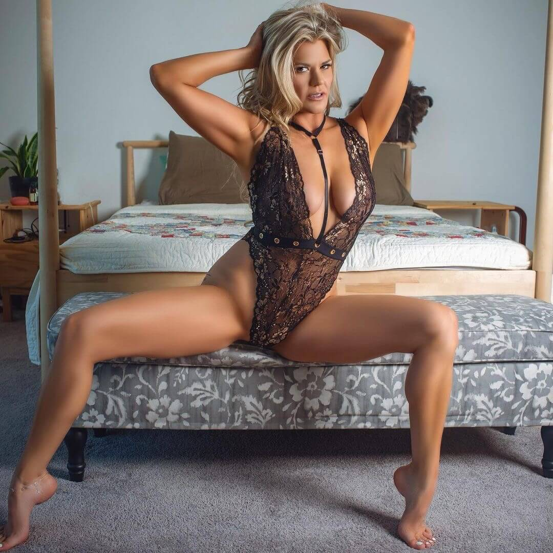 Hot Austin blonde model showing her tanned cleavage holding her arms up wearing black lingerie sitting bare feet on her bed with her legs wide open for a boudoir photo session