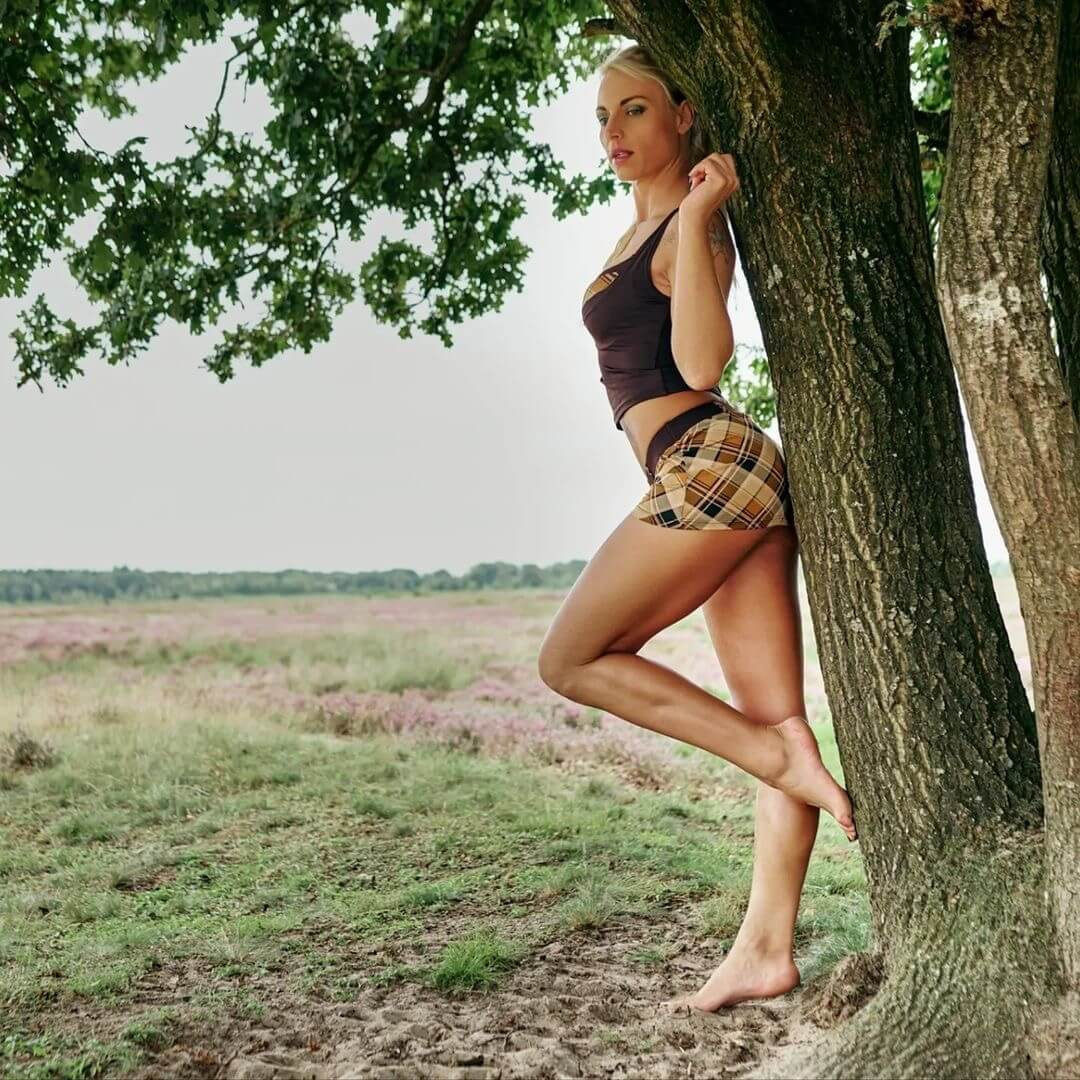 Hot inked blonde model wearing a short tight skirt showing her long sexy legs leaning bare feet on a tree