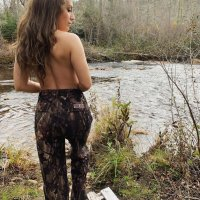 Hot and sexy canadian model standing topless outside wearing camouflage pants in front of a river