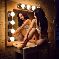 Sexy Canadian model sitting bare feet in her Calvin Klein underwear looking in a mirror showing her hot legs