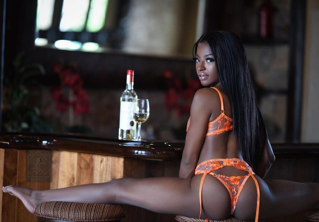 Hot black model sitting at the bar with her legs wide open showing some sexy booty wearing peach lingerie