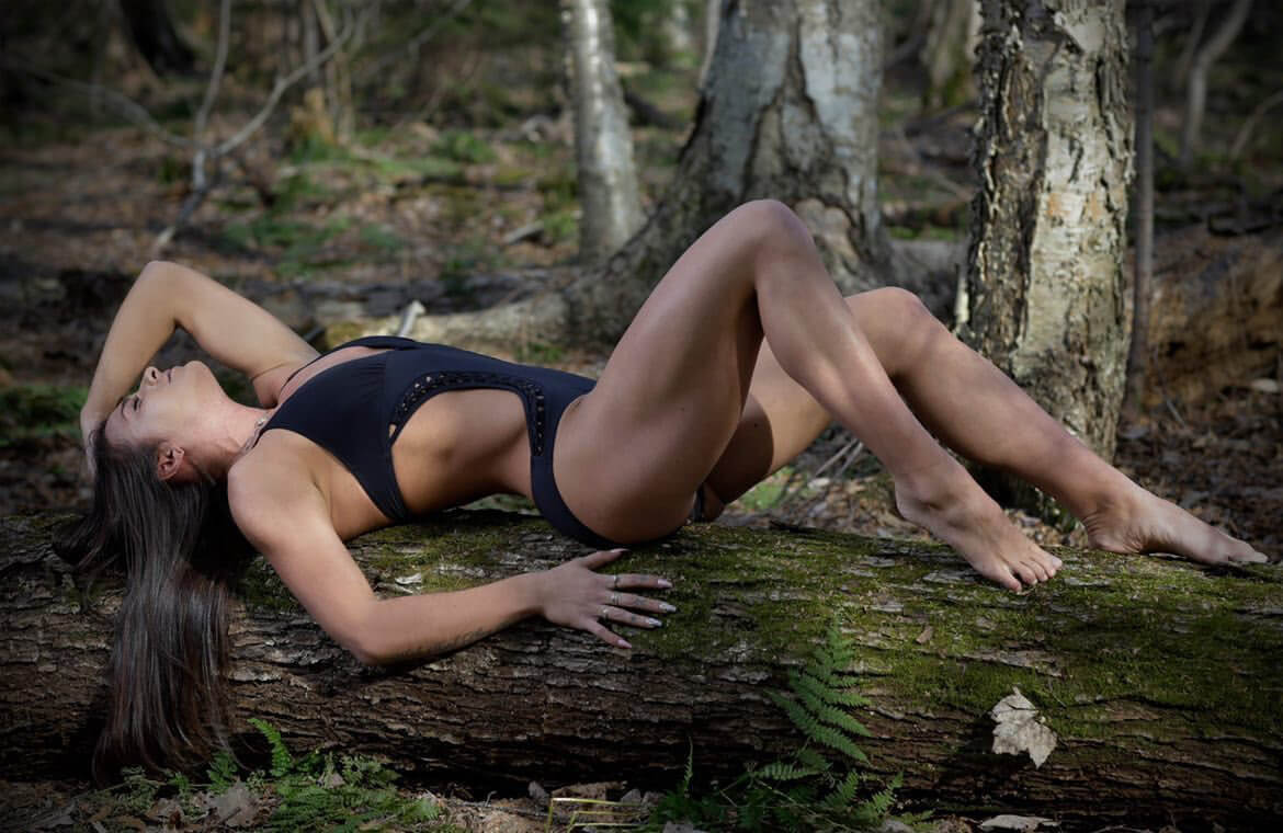 Sensual fitness model wearing a black swimwear showing her long sexy legs lying on a log bare feet in the woods