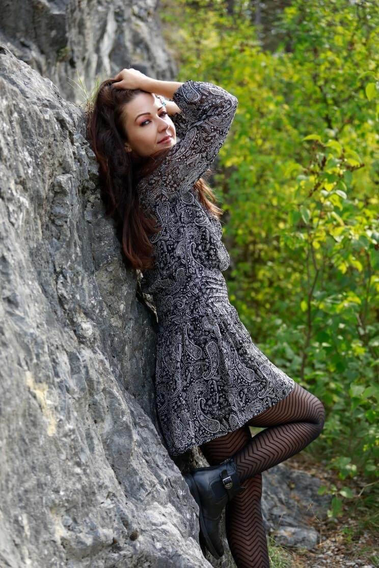 Sensual slavic milf wearing a short grey dress with black nylons showing her sexy legs leaning on a rock
