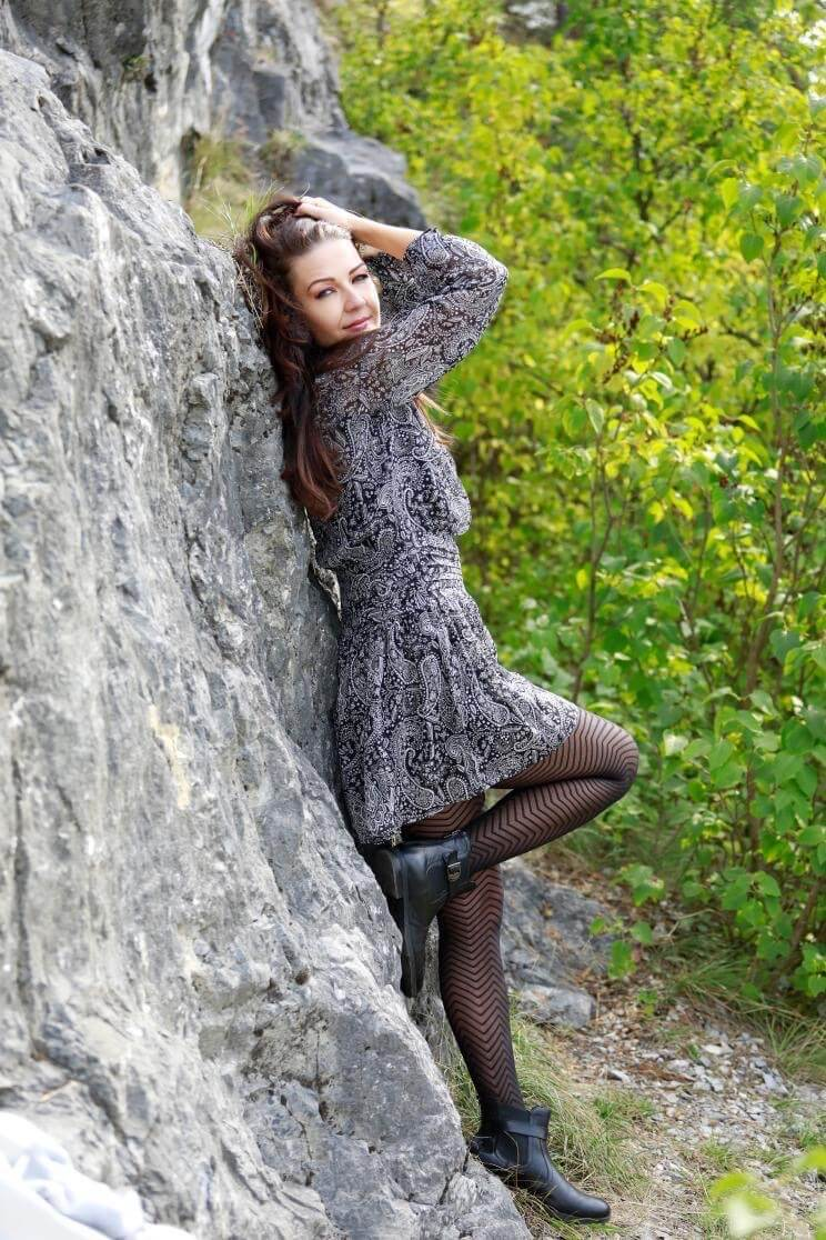 Beautiful slavic model wearing a short grey dress with black nylons showing her sexy legs leaning on a rock