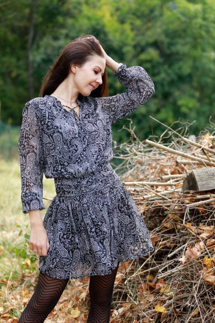 Beautiful slavic model wearing a short grey dress with black nylons brushing her hair in the country