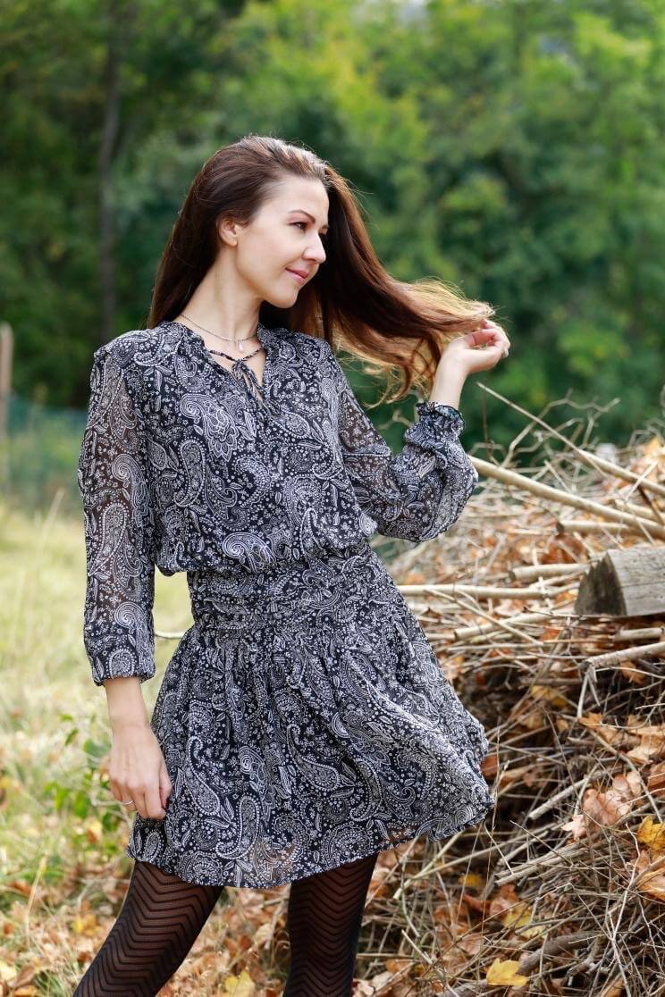 Beautiful slavic model wearing a short grey dress with black nylons out in the field