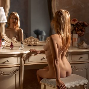 Beautiful blonde woman sitting in the nude in front of a vintage dresser for a boudoir photoshoot