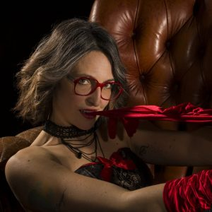 Beautiful mature tattooed woman Anny wearing black lingerie, giving the camera a sexy look with her red glove between her teeth