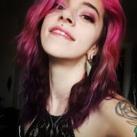 Beautiful pink haired smiling tattooed woman with hazel eyes Tora Reign wearing a short lace black transparent top smiling for a selfie