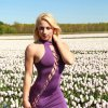 Beautiful dutch model Willeke Bartels wearing an open purple short dress in a flower field looking t the camera with one hand on her neck and a pokie nipple