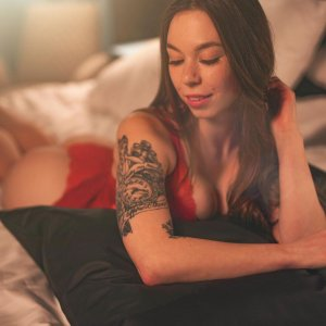 Beautiful inked brunette model Kätlin Angela @angela_modelpage showing her sexy cleavage wearing red lingerie in a boudoir photo session